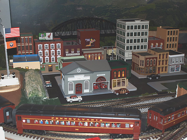A view of the layout buildings with a passenger train in the foreground.