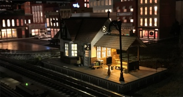 Layout photo of a small Woodland Scenics Frieght Depot lighted at night.
