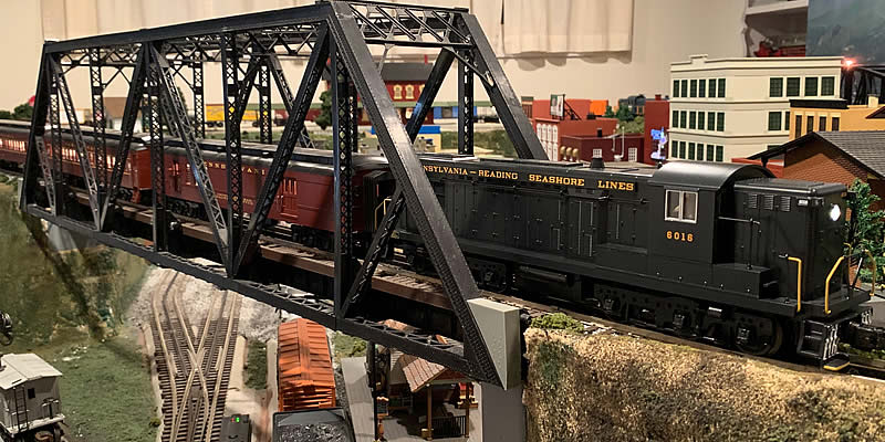 Photo of the layout with the PRSL-AS616 Locomotive pulling passenger cars across a girder bridge.