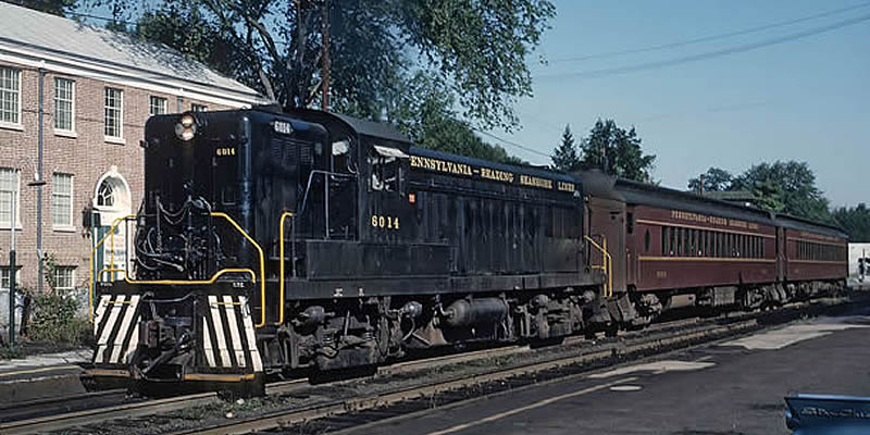 Photo of a real (full-size) PRSL locomotive pulling two passenger cars.